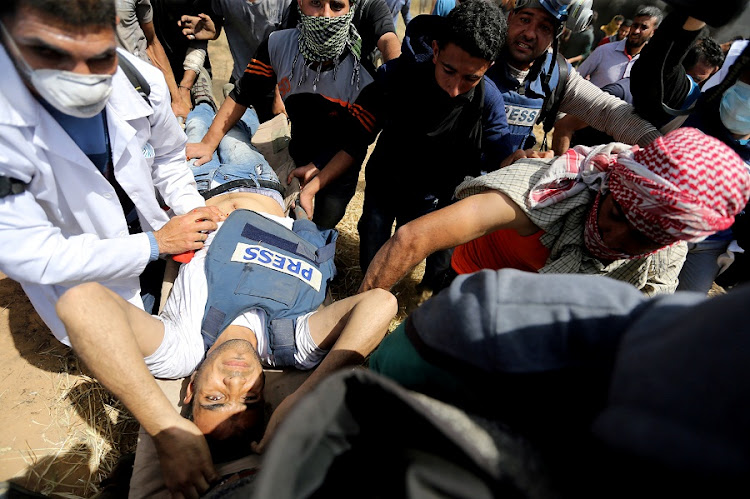 Wounded Palestinian journalist Yasser Murtaja is evacuated during clashes with Israeli troops at the Israel-Gaza border, in the southern Gaza Strip on Friday. He subsequently died of his injuries. Picture: REUTERS/IBRAHEEM ABU MUSTAFA