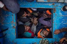 4 mannen onderdeks in kleine houten boot
