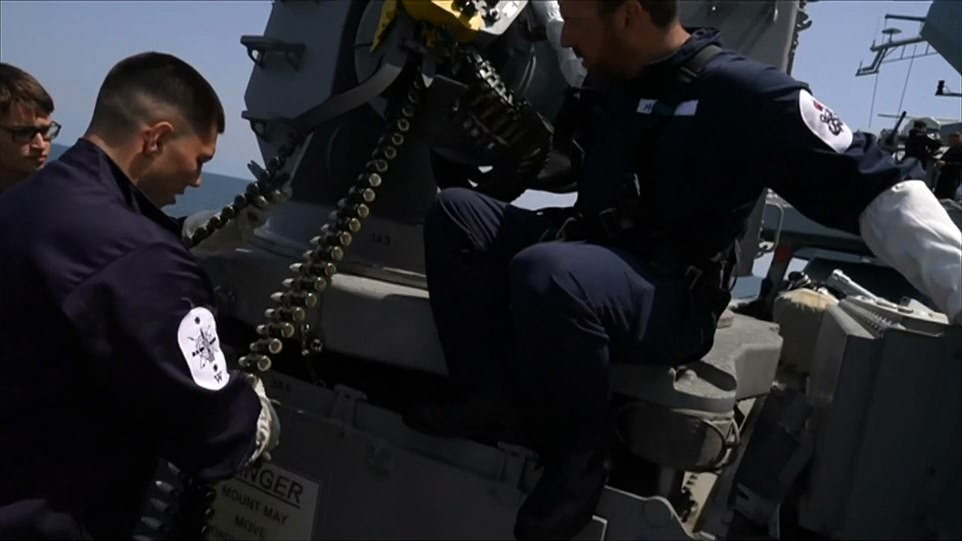 Heavy weaponry: Personnel get to grips with one of HMS Defender¿s formidable guns. They are pictured handling ammunition for one of the guns