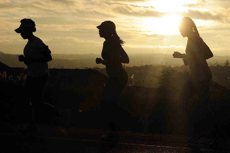 A group of social runners training for a marathon running in Olievenhoutbosch towards Centurion silhouetted by an early morning sunrise.