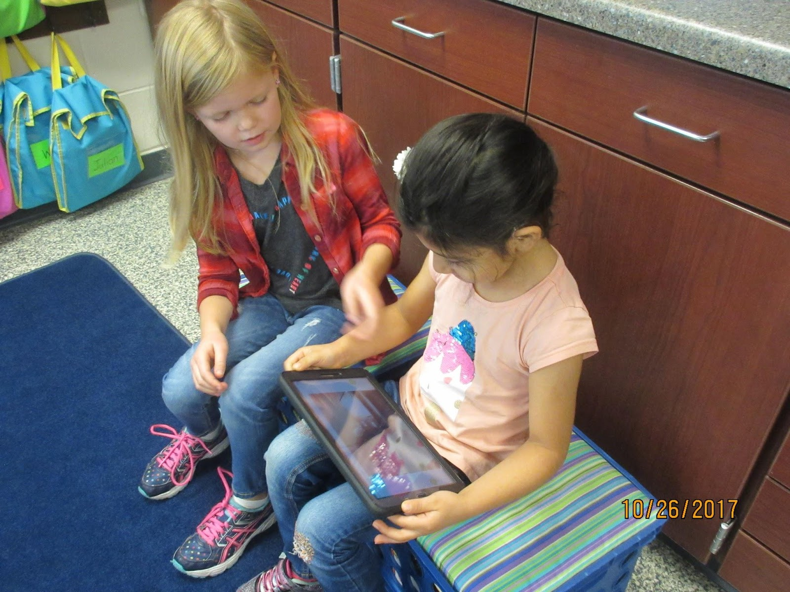 Students reading together from tablet