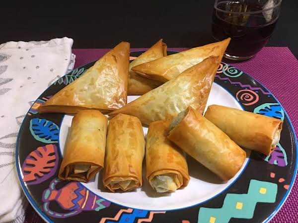 Stuffed Rolls And Triangles Sitting On A Plate.