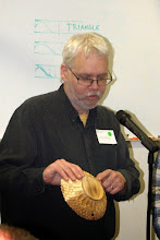 Photo: Joe Barnard discusses the carving on his osage orange bowl.