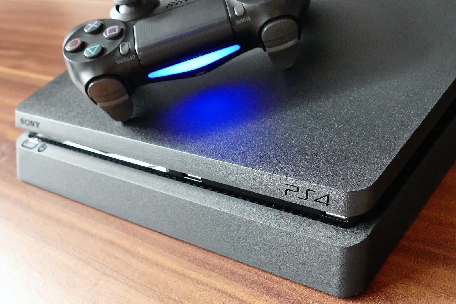 PS4 console and a DualShock 4 Wireless Controller with a glowing blue light bar