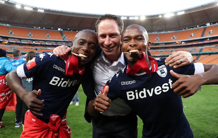 Bidvest Wits general manager Jonathan Schloss is flanked by midfielders Ben Motshwari (L) and Phumlani Ntshangase (R) as Wits were crowned the 2016/2017 Absa Premiership Champions after a match against Kaizer Chiefs at the FNB Stadium, Johannesburg South Africa on 27 May 2017.