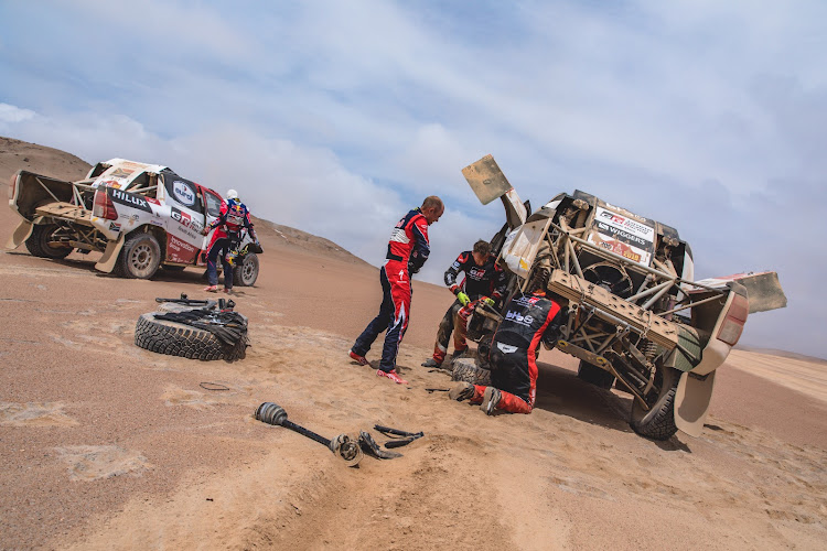 Giniel de Villiers and his navigator Dirk von Zitzewitz stop to assist their stricken Toyota team-mates Bernhard Ten Brinke and Xavier Panseri in the Peruvian desert. Picture: SUPPLIED