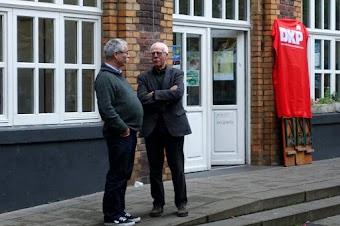 Zwei Genossen vor dem Eingang der Tagungsstätte, daneben an der Wand DKP-Fahne.
