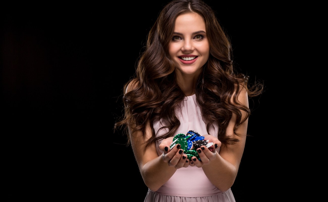 Female Poker player holding a handful of poker chips