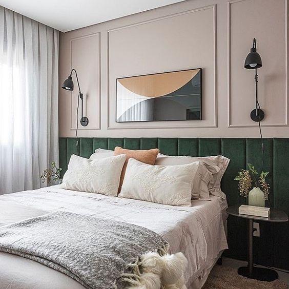 Quarto de casal com cabeceira aveludada na cor verdes, paredes rose com luminárias e mesinha de canto pretas.