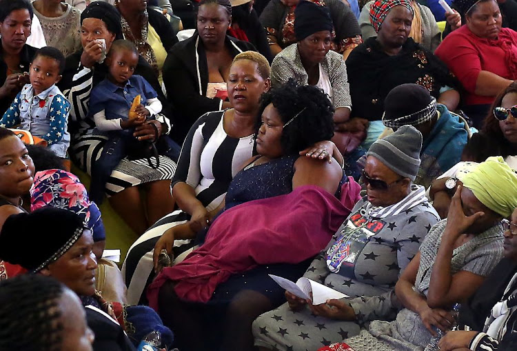 Relatives comfort each other at a memorial service for the hawkers who died