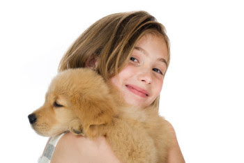 Nine year old girl holding puppy