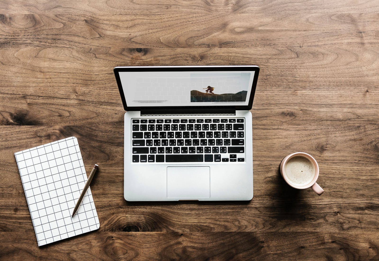 An open laptop on a desk with a notepad and pen next to it on one side and a mug of cocoa on the other.
