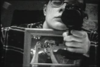 Photo: Self portrait I shot of my self wearing a photo of my Dad taking a photo of himself. I then film myself brushing my teeth, this was part of an assignment to do a self portrait in Super 8 mm film.