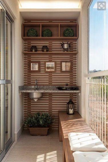Varanda pequena com pia pequena e griil elétrica, parede da pia com painel de madeira e acessórios decorativos, banco comprido de madeira e almofadas.