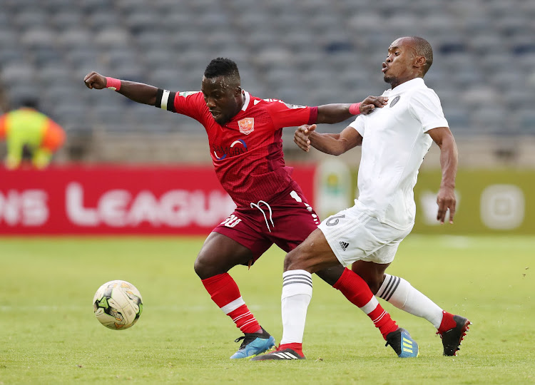 Mandela Ocansey (L) of Horoya is challenged by Asavela Mbekile of Orlando Pirates during the Caf Champions League match at the Orlando Stadium in Soweto on January 18 2019.