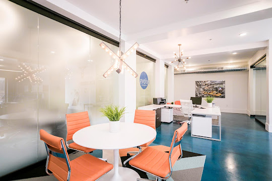 White round table with 4 orange chairs behind leasing desk in community leasing center