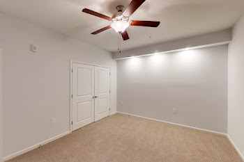 Bedroom with plush carpet, ceiling fan, and closet