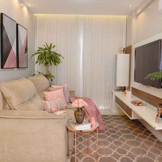 Sala moderna em tons rosa com sofá, quadros decorativos, plantas e painel com TV.