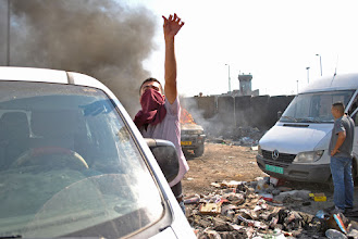Photo: A Palestinian youth directs attention to the flaming truck.