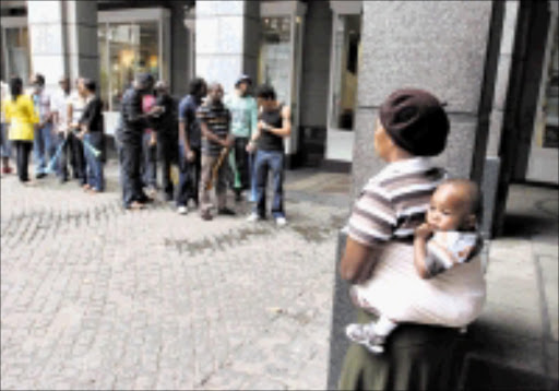 FOOTBALL MANIA: A woman with a child on her back watches a queue outside a bank in downtown Johannesburg during a promotion as the first ticket sales for the 2010 Soccer World Cup in South Africa kicked off on Friday. 20/02/09. Pic. Denis Farrell. © AP.