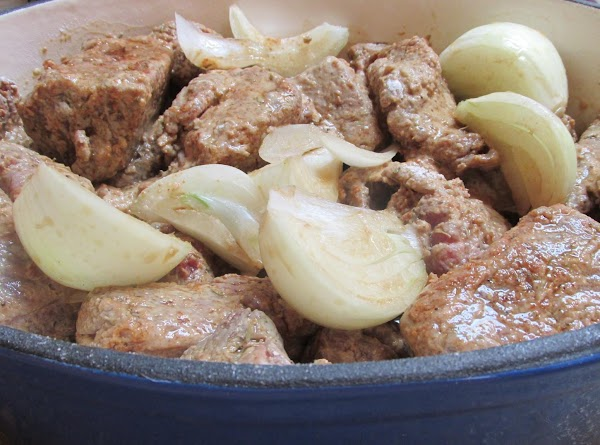 Add the seasoned meat cubes on top of onions, and add any excess flour...