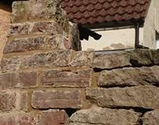Bricks and lime mortar topping a dry stone wall in Berkeley, Gloucestershire