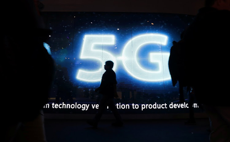 A visitor walks past a 5G sign during Mobile World Congress in Barcelona, Spain. Picture: REUTERS