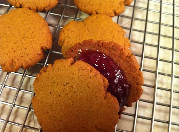 While still warm take two cookies, spread one with jam and stick together to...