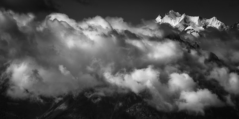 Photo: Above The Clouds (view large) From my blog: http://www.niophoto.com/above-the-clouds/  This image features the Swiss mountains Dom, Nadelhorn and Täschhorn. Three beautiful alpine peaks with a height of more than 4300 meters (14000ft). They are amongst the highest in Switzerland. I shot this image early in the morning. The light was still nice and soft and the fog and clouds just started to rise from the valley, adding a nice dose of drama to the scene. I was high up a mountain on the other side of the valley just at the right time.  I captured this image with my Nikon 70-200 f/2.8 VRII lens. A lens with which I have a love-hate relationship. I almost always stuff it in my bag, next to 2 or 3 other lenses, when I go hike up a mountain. From a physical point of view, I always regret that at the end of a day … it is just too darn heavy. When I come home though and see the quality it delivers, I am always glad I did take it. I would love to own a good light weight alternative lens though. Tips are welcome!  No filters were used upon capture. The image was processed in Lightroom 4.1 and Silver Efex Pro 2. I felt the image begged for a black and white conversion. I opted for a 2:1 crop to make the composition as strong as possible. Hope you like it :)  #BWFineArtLE by +Joel Tjintjelaar #BreakfastClub +Breakfast Clubby +Gemma Costa #PlusPhotoExtract by +Jarek Klimek, #monochromeMonday by +Manuel Votta+Nurcan Azaz+Jerry Johnson+Hans Berendsen,  #mountainmonday by +Michael Russell, +Landscape Photographyby +Margaret Tompkins,  #10000photographersaroundtheworld +10000 PHOTOGRAPHERSby +Robert SKREINER,  #AerialPhotography +AerialPhotographyby +Markham Lane #mouıntainphotos +Mountain Photosby +Baki Karacay #D800E  #bwfineart #bwphotography