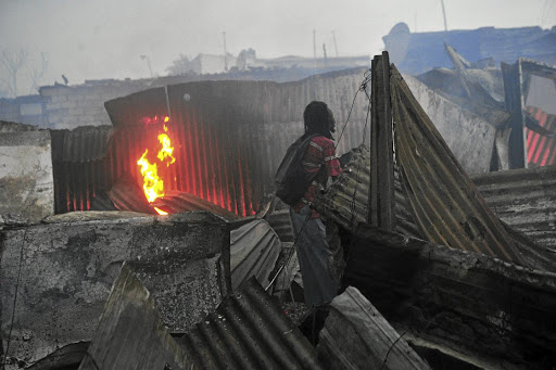 A resident watches as his shack goes up in smoke in Alexandra, Johannesburg, yesterday. / Veli Nhlapo
