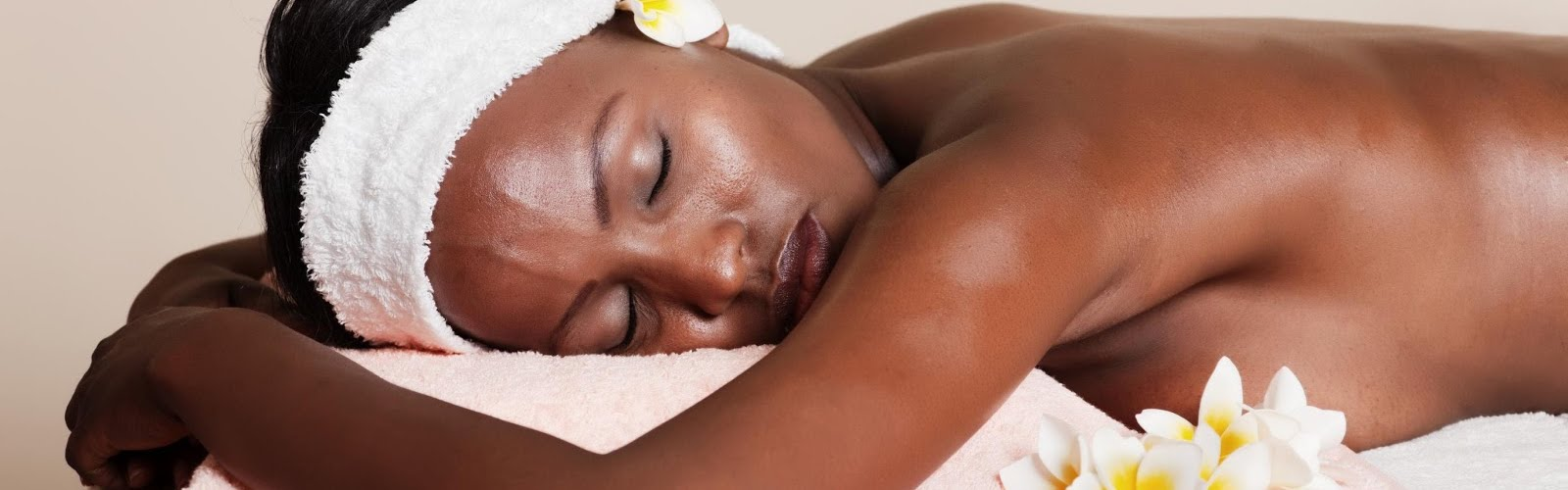 a woman of colour lying peacefully after having received a massage