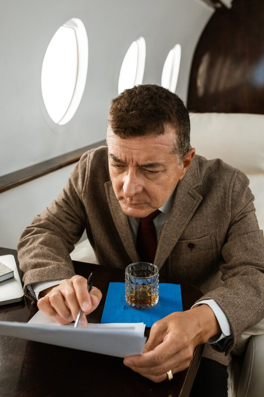 Man drinking alcohol on a plane
