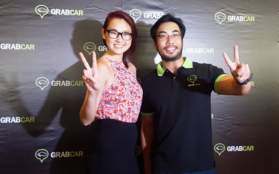GRABCAR PHILIPPINES HEAD NATASHA BAUTISTA AND GRABTAXI MANAGING DIRECTOR BRIAN CU FLASH THE NUMBER 2 SIGN SIGNIFYING GRABTAXI'S TWO YEARS OF SAFE, CONVENIENT, AND AWESOME RIDES