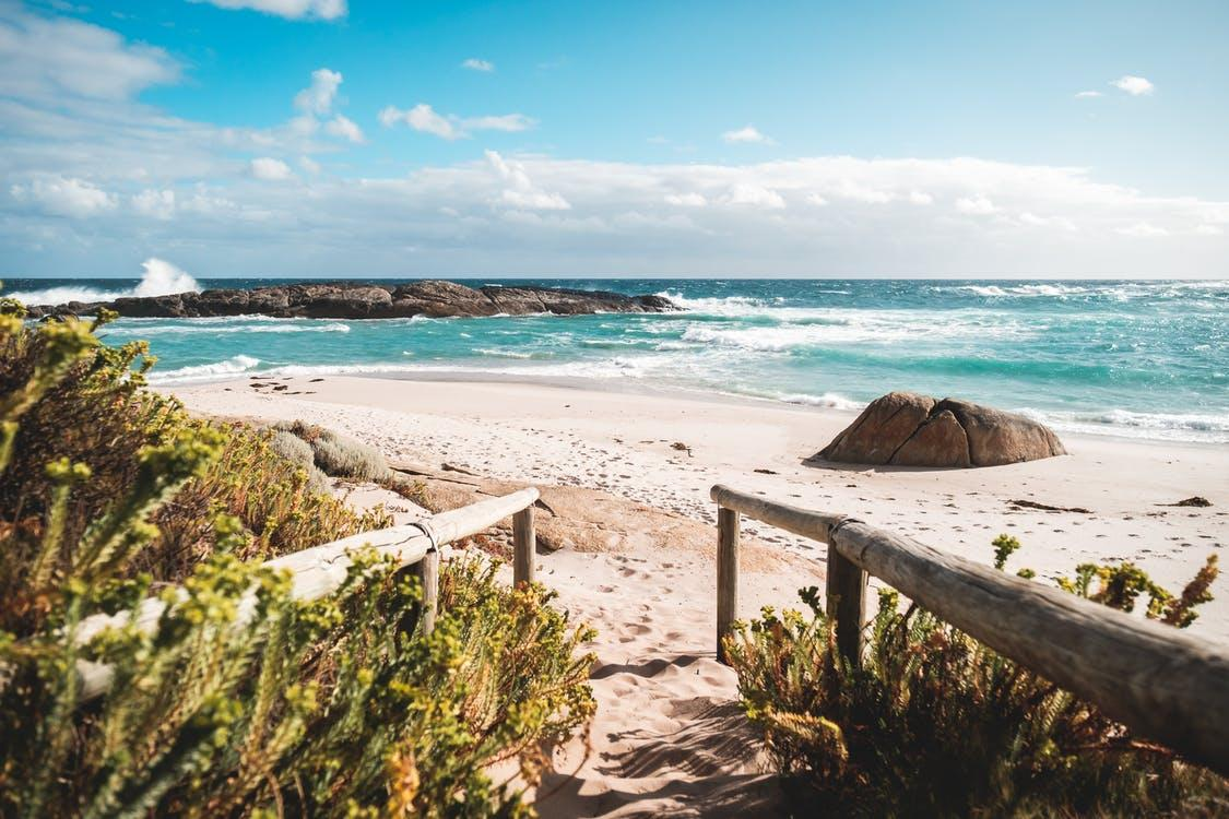 Picturesque view of footpath with wooden railings leading to sandy shore of turquoise water