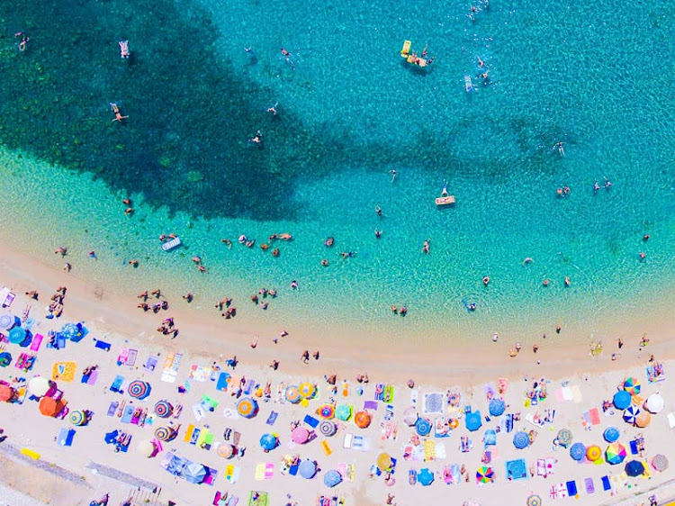 People sunbathing on the beach on Corfu island in Greece.