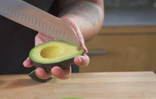 To cut avocado into chunks, using a chef's knife take the half...