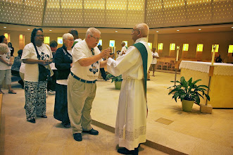 Photo: Deacon Raymond Derouen offers the Blood of Christ to ASBS pilgrims