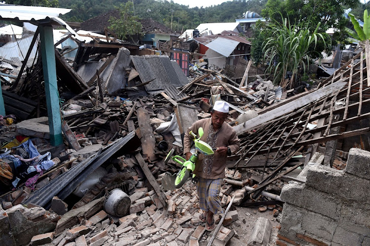 A man carries a small bicycle through the ruins of houses damaged by an earthquake in West Lombok, Indonesia on August 6 2018. Picture: REUTERS/ANTARA FOTO