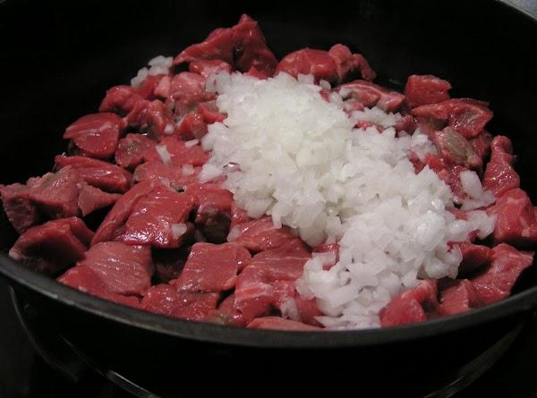 Over a medium heat; brown stew meat in olive oil in dutch oven; add...