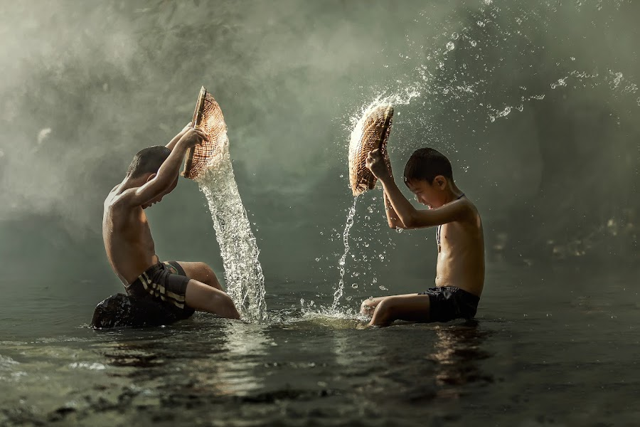 Thai boys splashing with friend in a river. by Jakkree Thampitakkul - Babies & Children Children Candids ( kids playing in summer, #2015 #color image #composition #friendship #happiness #horizontal #male friendship #motion #nature #outdoors #photography #rural scene #southeast asia #splashing #sports equipment #summer #thai culture #thailand #tropical climate #wet )