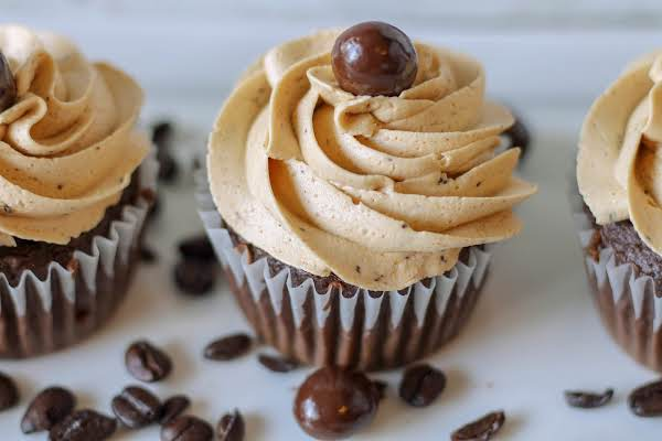 Easy Coffee Icing Piped Onto Chocolate Cupcakes With A Chocolate Covered Coffee Bean On Top.