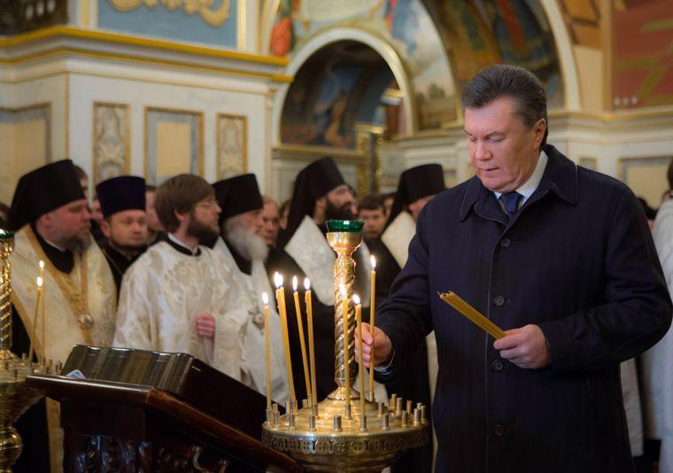 Бывший президент Украины Виктор Янукович ставит свечу во время богослужения по случаю Дня соборности и свободы в Успенском соборе в Киеве, 22 января 2014 года