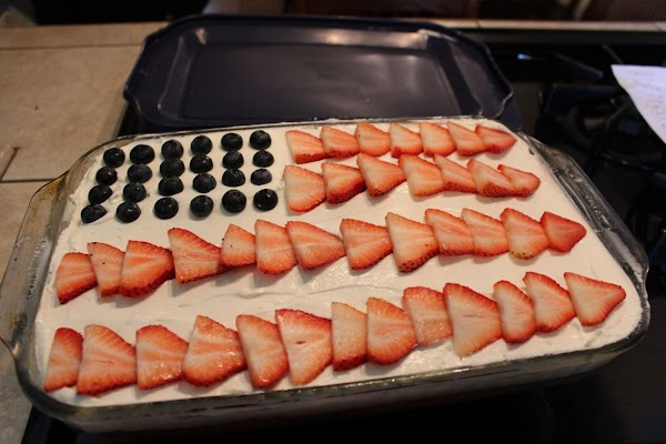 Top with fresh blueberries and sliced strawberries. Either serve or cover and put back...