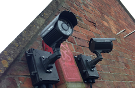 two security cameras on a facebrick wall