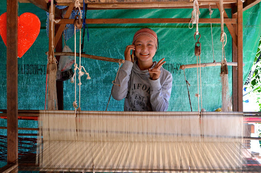 A girl gestures in a silk weaving cooperative originally set up for war widows.
