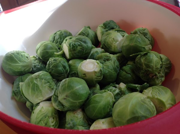 Trim Brussels sprouts and cut in half for easier cooking if desired. Slice the...