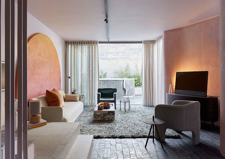 The living area is anchored by a chunky loop rug and a three-seater sofa. The arch-shaped artwork is by Rosie Mudge.