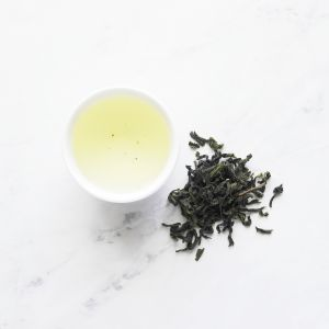 image of baozhong dry tea, next to a cup of brewed baozhong