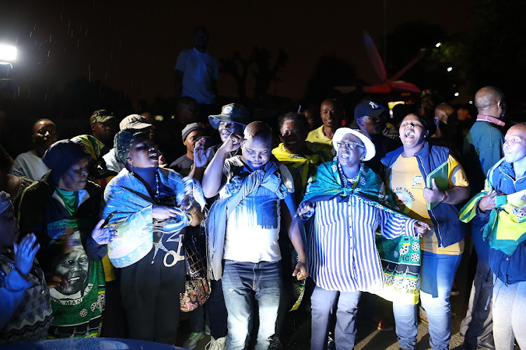 South Africans pay their respects outside the Soweto home of Winnie Madikizela-Mandela on Monday night. Picture: ALON SKUY​