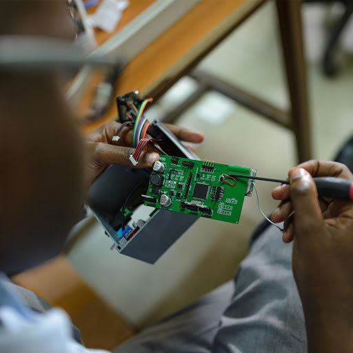Engineer building a sensor in his lab at Makerere University
